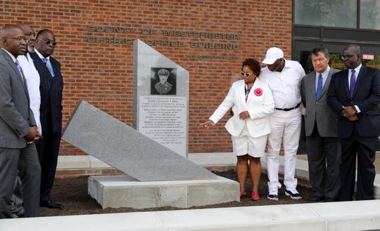 Parents Stan Ridley, second from left, and Felita Bouche, fourth from left, look at the memorial as friends and relatives of Mount Vernon Detective Christopher Ridley, gather on Court Street in White Plains, Aug. 31, 2019, for an unveiling of a memorial to the police officer who was killed on January 25, 2008.
