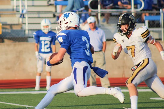 Windthorst quarterback Cy Belcher runs it himself in the season opener against Henrietta.