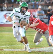 Iowa Park quarterback Trent Green (1) tries to get away from Holliday's Cason Foster (52) during Frinday night's game in Holliday.