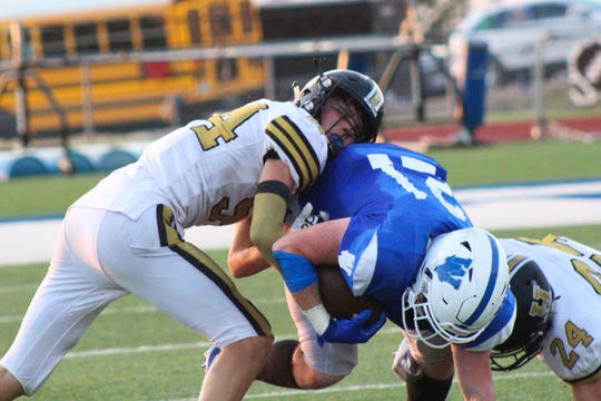 Henrietta's Reece Hensley (left) and Bryce Sikes team up to bring down Windthorst's Awtry Blagg.