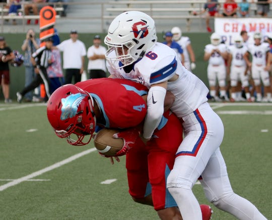 Hirschi's Isaiah Wilson is tackled by Graham's Trey Overcash Friday, Aug. 30, 2019, at Memorial Stadium.