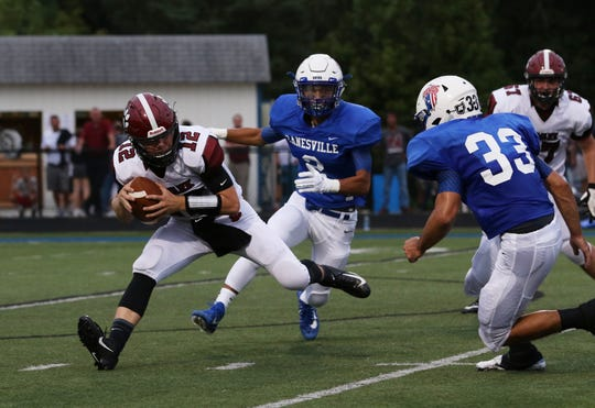 Newark quarterback Jake Sherman tries to elude Zanesville's Gaige Barnett and Zarek Morgan last week. The Blue Devils shut out the Wildcats, and turn their focus to the physical run game of Johnstown.