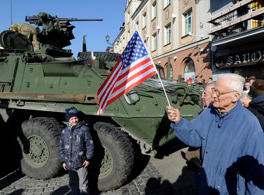 In this Tuesday, March 24, 2015, photo, a man holding a U.S. flag walks past a U.S. Army Stryker armored vehicle from the 3rd Squadron of the 2nd Cavalry Regiment, during their stop to meet local residents on the Kosciuszko Market Square in Bialystok, Poland.