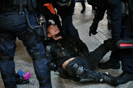 Police arrest a protester in the Causeway Bay area of Hong Kong on Aug. 31, 2019, as people demonstrate, defying a ban on rallying -- and mounting threats from China -- to take to the streets for a 13th straight weekend.