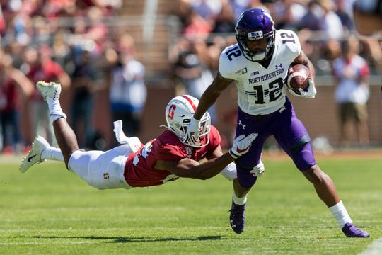 Stanford Cardinal cornerback Obi Eboh tackles Northwestern Wildcats wide receiver JJ Jefferson (12) in the second quarter at Stanford Stadium.