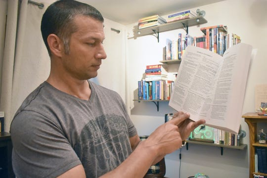 Ryan Ramnarace reads from a book in his home office July 24, 2019. While serving a 14-year prison sentence, Ramnarace found inspiration in various books about the criminal justice system and hope for a meaningful life after prison.