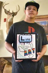 Marcus Howell holds a piece of artwork July 24, 2019, inside his Portage, Wis. home. His father is serving a prison sentence in Michigan, and drawing art helps them communicate creatively and share new ideas with one another.