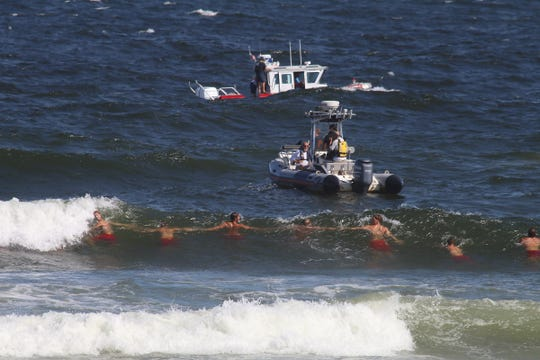 Lifeguards form a chain as they search for a missing 15-year-old boy who was pulled into the ocean near the Newark Avenue jetty in Spring Lake Sunday afternoon, September 1, 2019.
