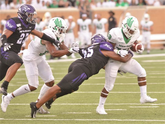 ACU linebacker Qua'Shawn Washington, an Abilene High grad, wraps up North Texas' DeAndre Torrey during the Wildcats' game Saturday, Aug. 31, 2019, at Apogee Stadium in Denton.