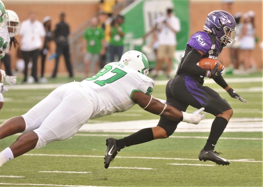 North Texas' Dion Novil, a Wylie grad, tries to trip up ACU receiver Kobe Clark, a Sweetwater grad, during their game Saturday at Apogee Stadium in Denton.