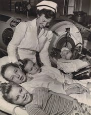 A nurse administers to the Hartley girls, Ruth Elizabeth, 5; Peggy Ann, 12; and Mary Sue, 7, while Doris Hartley, 10, lies in the iron lung in 1953.