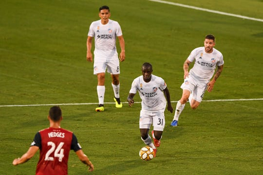 Aug 31, 2019; Frisco, TX, USA; FC Cincinnati forward Kekuta Manneh (31) plays the ball as FC Dallas defender Matt Hedges (24) looks on during the first half at Toyota Stadium.