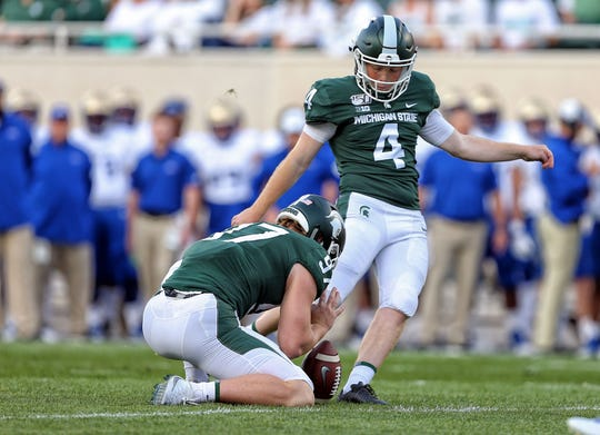 Aug 30, 2019; East Lansing, MI, USA; Michigan State Spartans place kicker Matt Coghlin (4) kicks an extra point out of the hold by place kicker Tyler Hunt (97) during the first quarter of a game at Spartan Stadium.