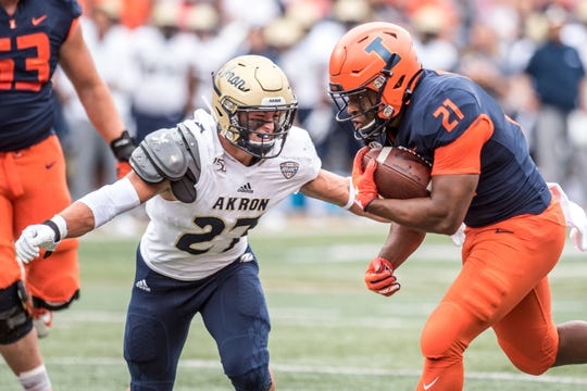 Illinois running back Ra'Von Bonner (21) maneuvers past Akron defender Bubba Arslanian (27) in the first half of an NCAA college football game, Saturday, Aug. 31, 2019, in Champaign, Ill.
