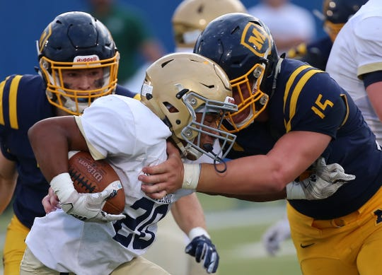 Moeller's Nate Pabst (15) tackles Cathedral's Daylen Hall during their   football game Saturday, Aug. 31, 2019.