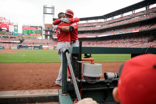 Cincinnati Reds' Eugenio Suarez gets a hug from teammate Jose Iglesias (4) after hitting a two-run home run during the third inning in the first baseball game of a doubleheader against the St. Louis Cardinals Sunday, Sept. 1, 2019, in St. Louis.