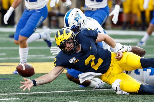 Michigan quarterback Shea Patterson fumbles during the first half against Middle Tennessee State at Michigan Stadium, Saturday, August 31, 2019.
