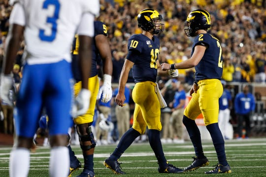 Michigan quarterback Dylan McCaffrey (10) talks to quarterback Shea Patterson (2) before an extra point attempt during the second half at Michigan Stadium in Ann Arbor, Saturday, August 31, 2019.