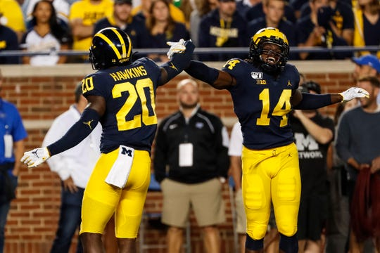 Michigan defensive backs Josh Metellus (14) and Brad Hawkins (20) celebrate a play against Middle Tennessee State during the first half at Michigan Stadium, Saturday, August 31, 2019.