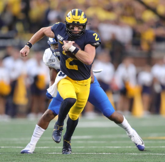 Michigan Wolverines quarterback Shea Patterson runs for a first down against the Middle Tennessee State Blue Raiders during the first half Saturday, August 31, 2019 at Michigan Stadium.