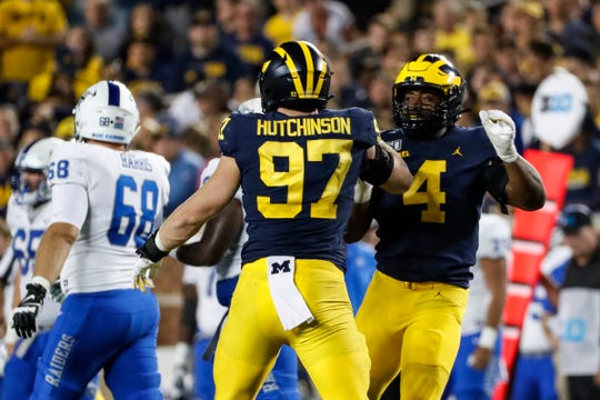 Michigan's Aidan Hutchinson (97) and Michael Danna (4) celebrate a play against Middle Tennessee State during the second half at Michigan Stadium in Ann Arbor, Saturday, August 31, 2019.