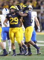 Michigan Wolverines' Jordan Glasgow (29) celebrates a tackle with Josh Ross vs. the Middle Tennessee State Blue Raiders, Saturday, Aug. 31, 2019 at Michigan Stadium.