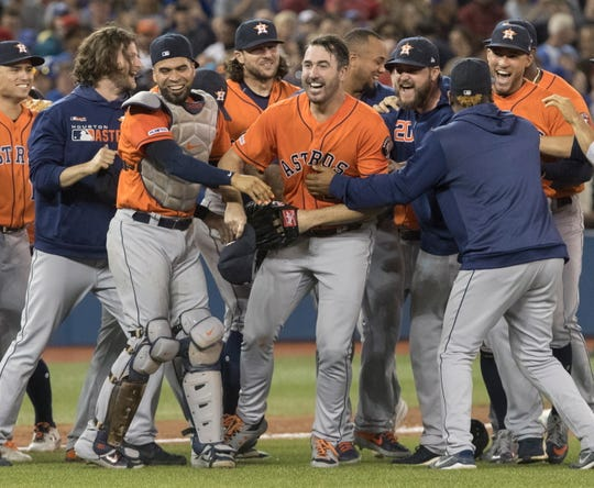 Astros starting pitcher Justin Verlander, center, is mobbed by teammates after pitching a no-hitter against the Toronto Blue Jays on Toronto, Sunday, Sept. 1, 2019.