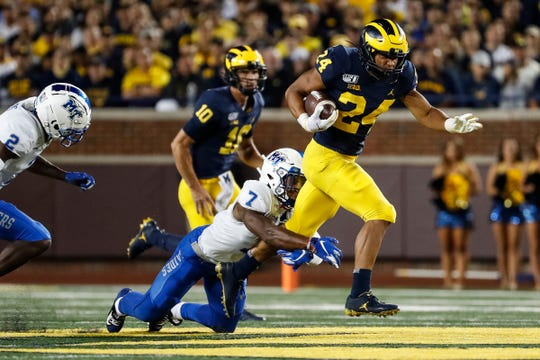 Michigan running back Zach Charbonnet runs against Middle Tennessee State safety Jovante Moffatt during the second half at Michigan Stadium in Ann Arbor, Saturday, August 31, 2019.