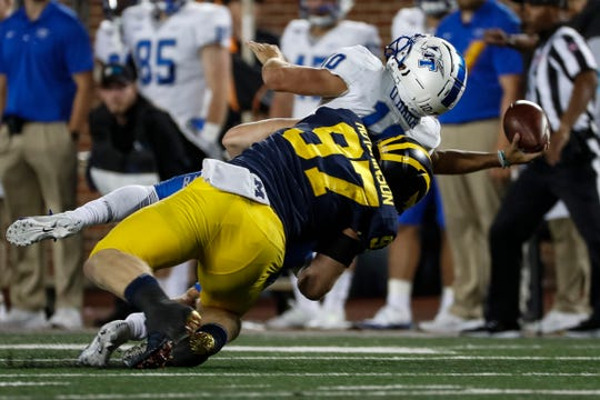 Michigan's Aidan Hutchinson tackles MTSU quarterback Asher O'Hara during the second half at Michigan Stadium on Saturday.