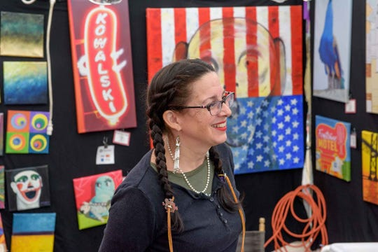 Julie Fournier, owner of Smiling Eyes Studio displays her original artworks at the Hamtramck Labor Day festival Sunday, Sept. 1, 2019.