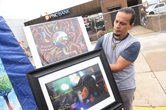 Artist Michael Rey, of BeloZero Visual Energy, displays his artwork at the 40th Hamtramck Labor Day Festival on Sunday.