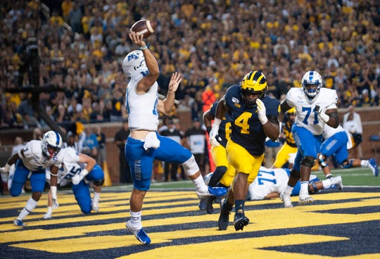 Michigan defensive lineman Mike Danna pressures Middle Tennessee State quarterback Asher O'Hara to throw an incomplete pass out of his own end zone in the first quarter last Saturday.