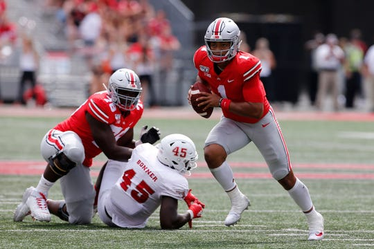 Ohio State quarterback Justin Fields, right, runs up field as teammate Nicholas Petit-Frere, left, blocks Florida Atlantic defensive end Tim Bonner during the second half on Saturday.