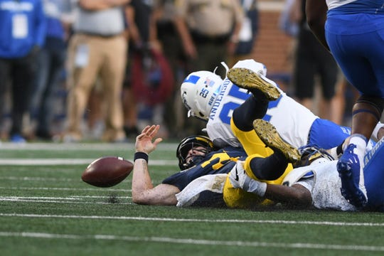 Michigan quarterback Shea Patterson fumbles the ball on the first offensive play of the game.