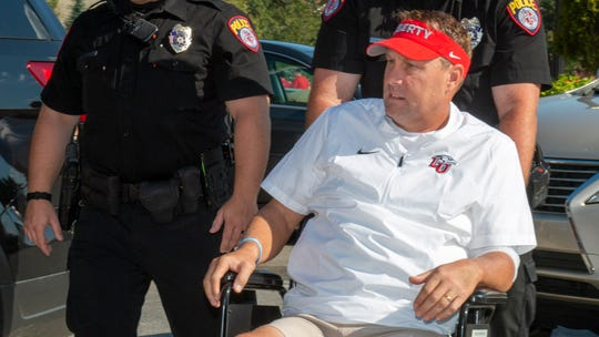 Liberty head football coach Hugh Freeze arrives to coach from a wheelchair in the coaches' box against Syracuse Saturday.