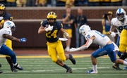 Michigan running back Zach Charbonnet rushes for a first down in the first quarter.