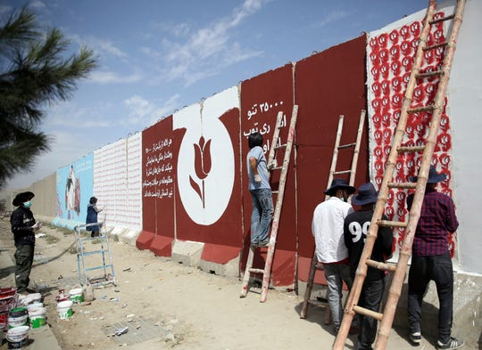 Independent Afghan artists paints tulips on blast walls in Kabul, Afghanistan, For almost a year, Afghanistan's more than 30 million people have been in the awkward position of waiting as a United States envoy and the Taliban negotiate their country's fate behind closed doors.
