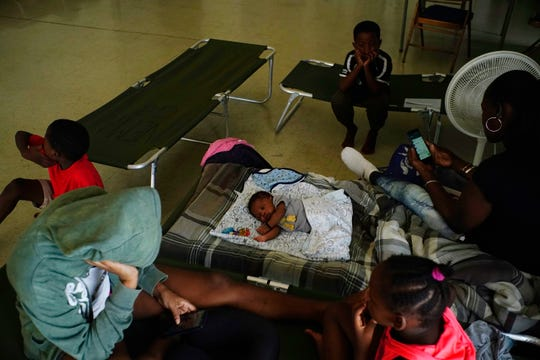 Anastacia Makey, 43, far right, and her family sits on cots inside a church that was opened up as a shelter as they wait out Hurricane Dorian in Freeport on Grand Bahama, Bahamas, Sunday.
