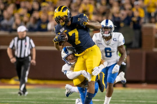 Michigan wide receiver Tarik Black tries to run the ball while being dragged to the ground by Middle Tennessee safety Reed Blankenship in the first quarter.