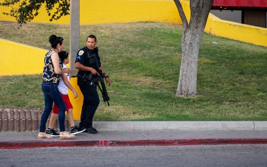 An Odessa police officer escort bystanders away from an area investigated for a shooting in Odessa, Texas, Saturday, Aug. 31, 2019, following a deadly shooting. Several people were dead after a gunman who hijacked a postal service vehicle in West Texas shot more than 20 people, authorities said Saturday. The gunman was killed and a few law enforcement officers were among the injured.