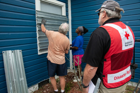 American Red Cross volunteer Bob Wallace shares a moment with resident Robert Murphy (orange shirt) as he and his landlords, Jackie and Bruce Foster, board up windows in advance of Hurricane Dorian. Each of the boards had been carefully marked as to which window they should shutter, indicating that this was not the first storm for them to provide protection.