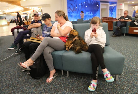 Debbie Turnebull of the UK sits with her children and four other family members. They originally were called on Friday saying their flight was moved to Wednesday, but then called again saying their flight was moved back to the original time, Sunday.  Orlando International Airport passengers were thankful they still had time to get out of Florida as Hurricane Dorian crawls closer to the east side of Florida, Sunday, September 1, 2019. Some were stranded some were leaving early. But yet a steady of vacationers still poured into Orlando, FL, looking to still enjoy Disney.