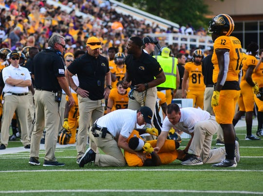 Athletic trainers attend to Southern Miss Golden Eagles Travinsky Mosley (22) during the first quarter against Alcorn State Aug. 31, 2019.