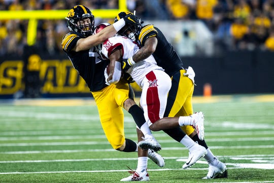 Iowa outside linebacker Nick Niemann, left, and strong safety Geno Stone make a tackle during Iowa's opening win against Miami. The Hawkeyes held Miami to 11 first downs.