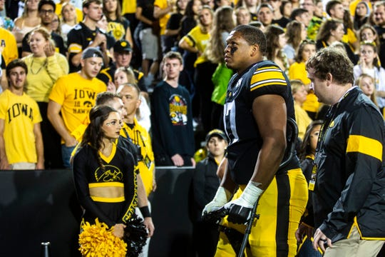 Iowa offensive lineman Alaric Jackson (77) walks off the field on crutches during a NCAA non conference football game, Saturday, Aug. 31, 2019, at Kinnick Stadium in Iowa City, Iowa.