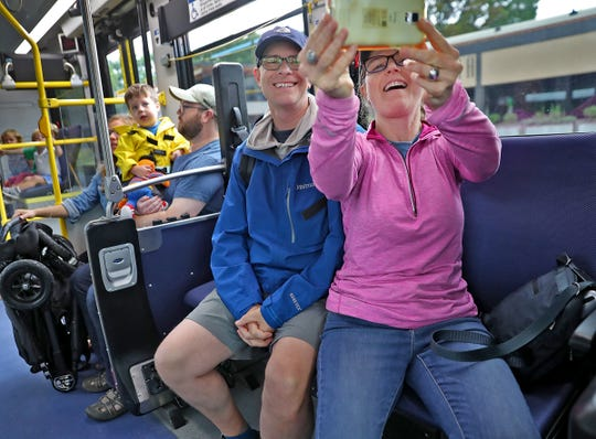 Mary Hayes, right, takes a photo of herself and Eric Gutter, as they ride a Red Line bus on opening day, Sunday, Sept. 1, 2019.