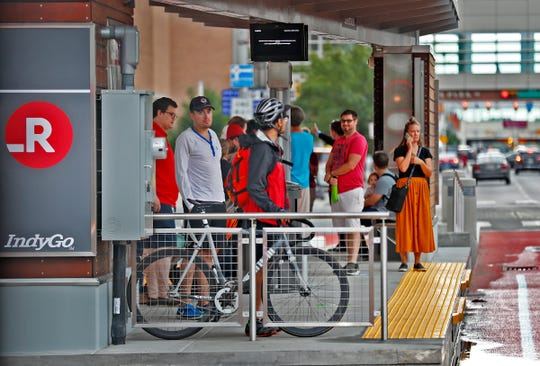 Riders of the IndyGo Red Line wait at standalone stations with real-time information monitors, shade, benches and ticketing kiosks.