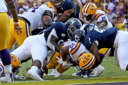 LSU running back Clyde Edwards-Helaire (22) scores on a 1-yard run as Georgia Southern's C.J. Wright (94) and Randy Wade Jr. (47) defend in the first quarter of an NCAA college football game in Baton Rouge, La., Saturday, Aug. 31, 2019. (AP Photo/Michael Democker)