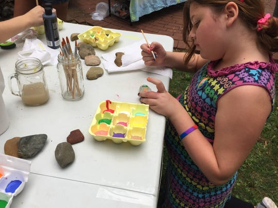 Lyla Helms, 10, of Lancaster, paints a Kindness Rock at the Pride event in downtown Lancaster Saturday.