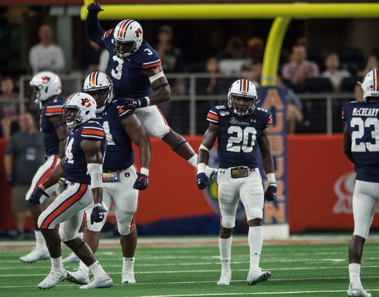 Auburn defensive lineman Marlon Davidson (3) and Tyrone Truesdell (94) celebrate a big defensive stop at AT&T Stadium in Arlington, Texas, on Saturday, Aug. 31, 2019. Auburn defeated Oregon 27-21.